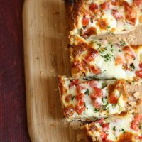 french bread pizza, sliced on a wooden cutting board