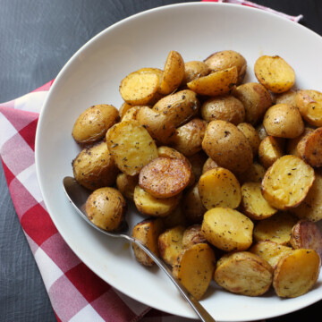 large serving bowl of roast potatoes with red checked cloth