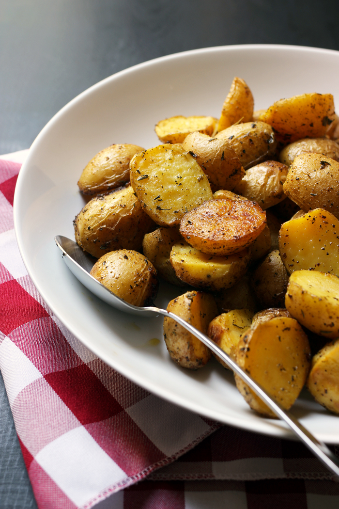 spoon in bowl of roast potatoes with red checked cloth