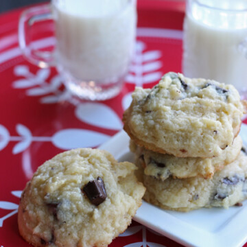A close up of a plate of cookies and cups of milk