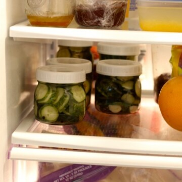 A close up of an open refrigerator filled with pickle jars