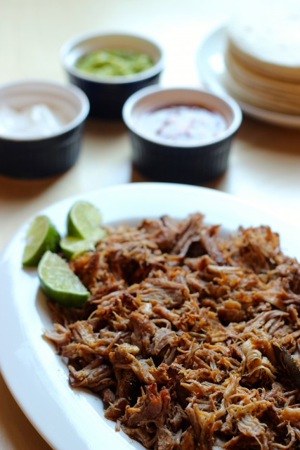slow cooker pork on a plate and ramekins of toppings