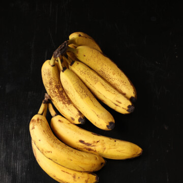 Bunch of bananas sitting on top of a wooden table