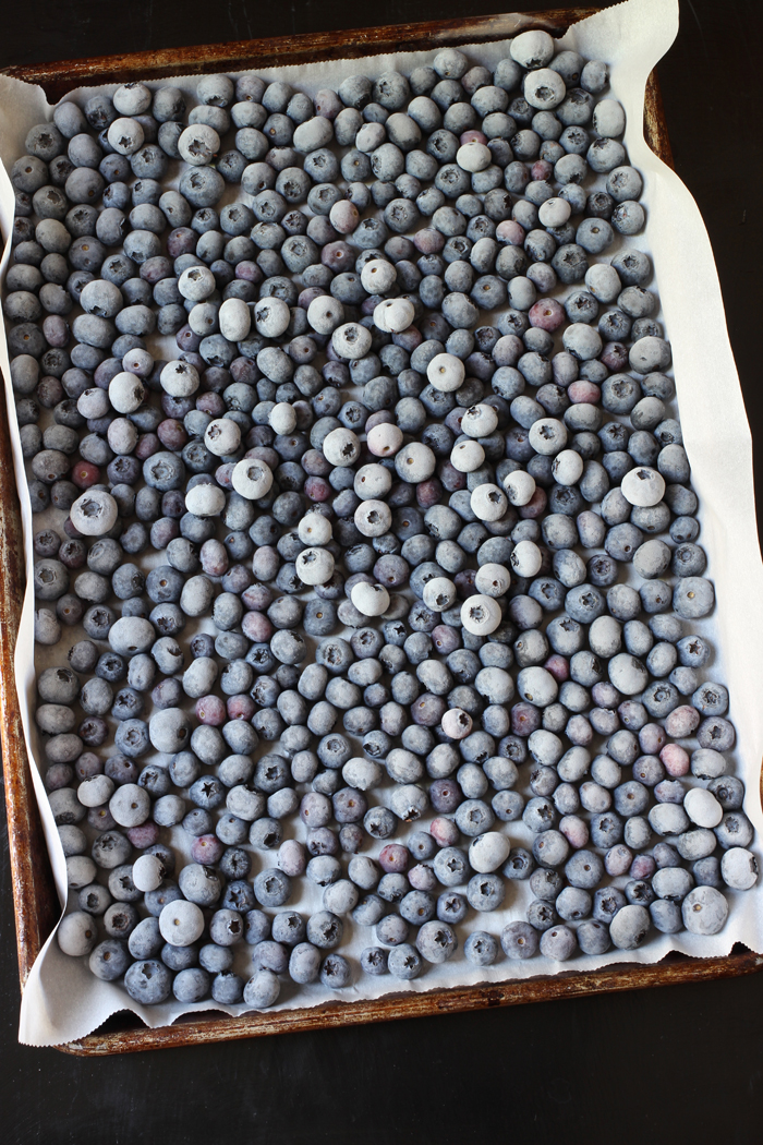 frozen blueberries on a rimmed, parchment-lined tray