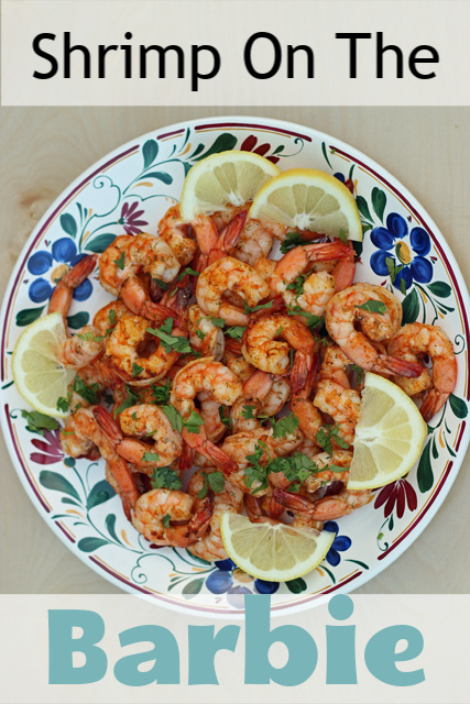 A plate of grilled shrimp and lemon wedges