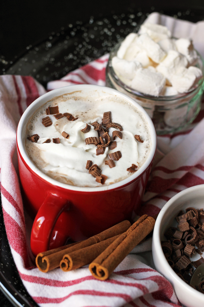 cocoa in red mug with whipped cream and chocolate alongside toppings