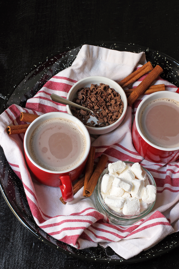 hot cocoa in red mugs on tray with toppings