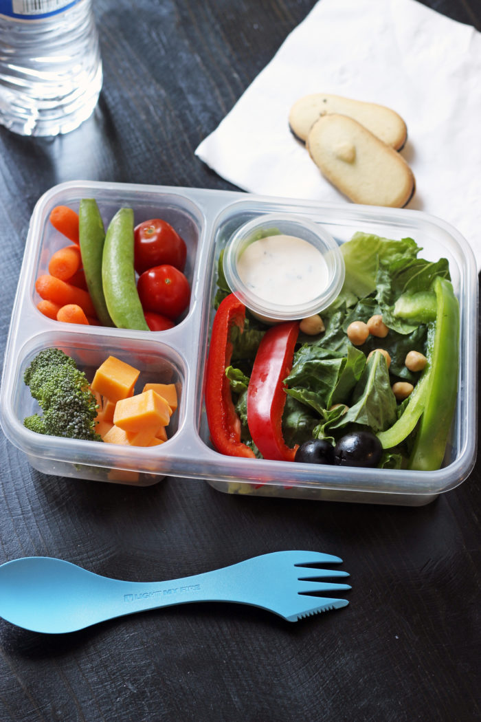 divided lunch box with cheese, vegetables, salad, and dip
