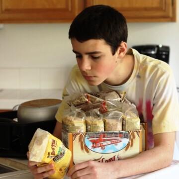 teen boy reading package of grains