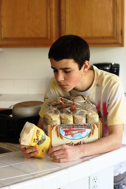 teen boy reading package of grains