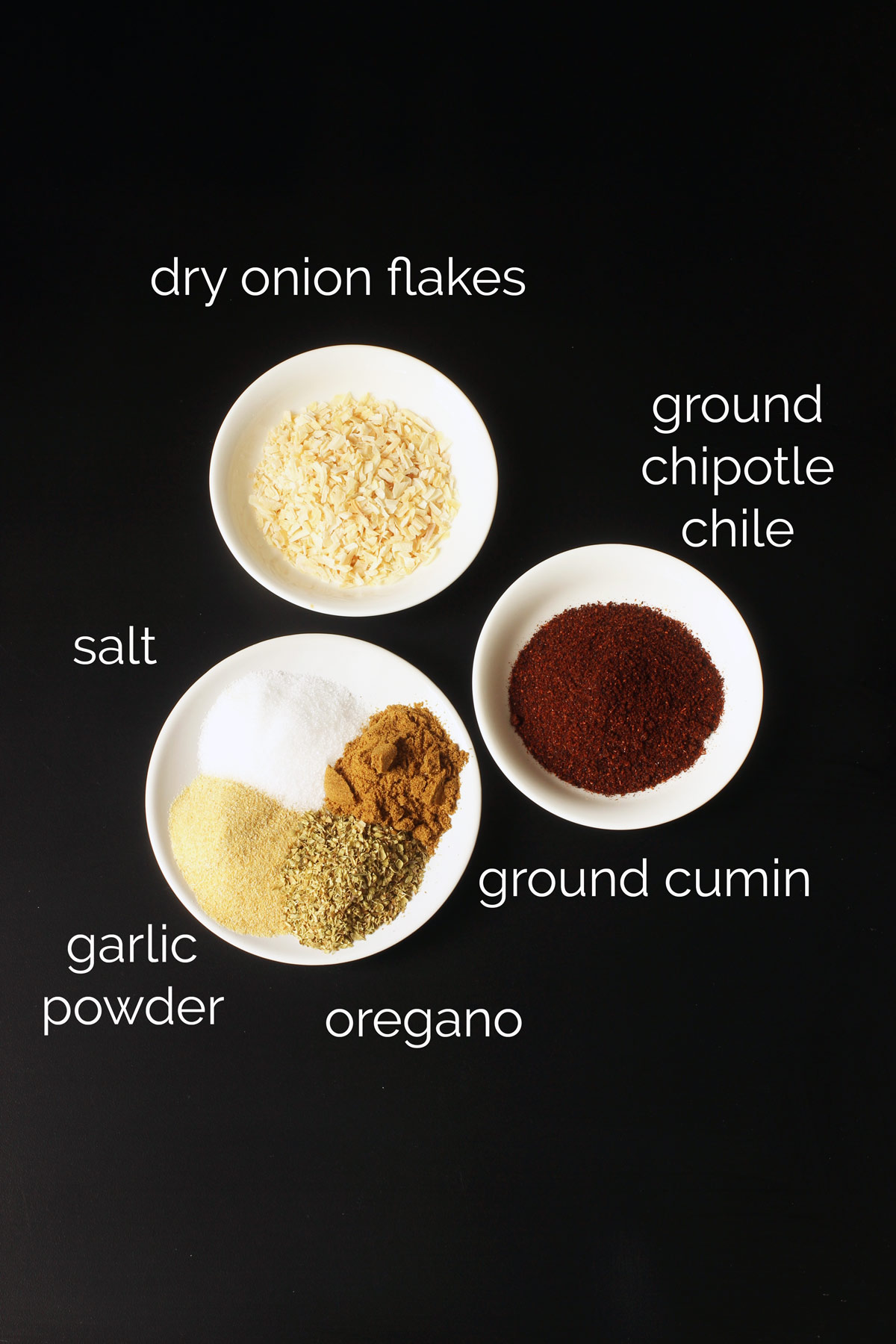 ingredients for chipotle seasoning in small white dishes on black table top.