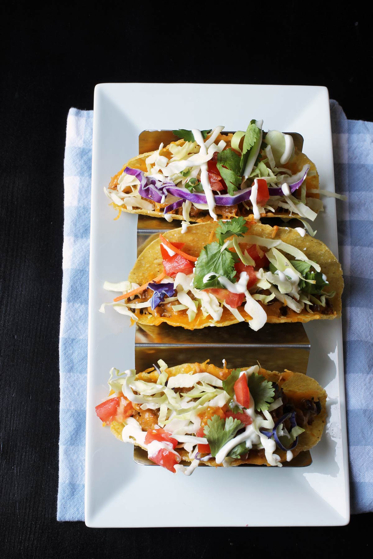 tray of three crunchy tacos on white platter with blue checked napkin.