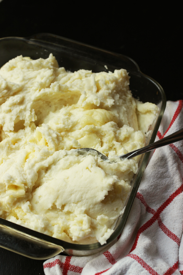 mashed potatoes in a glass dish with spoon
