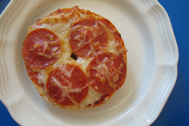 A close up of a pizza bagel on a plate