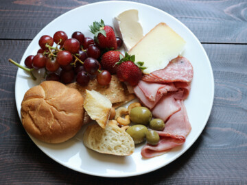 A plate with rolls, meat, and cheese