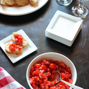 Bruschetta in a bowl with bread on plate