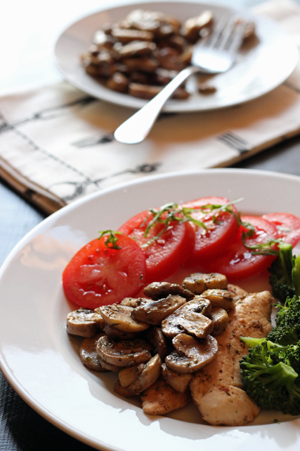 Herbed Sauteed Mushrooms on a dinner plate with chicken and sliced tomatoes