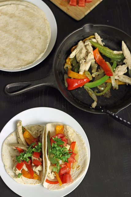 skillet of chicken fajitas, corn tortillas, and two fajitas on a plate