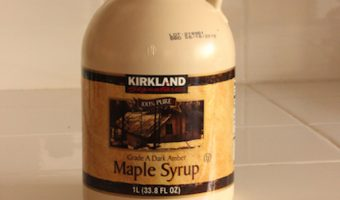 A jug of maple syrup sitting on a counter