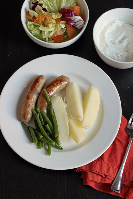 sausage, potatoes, and green beans on a plate with a salad next to it