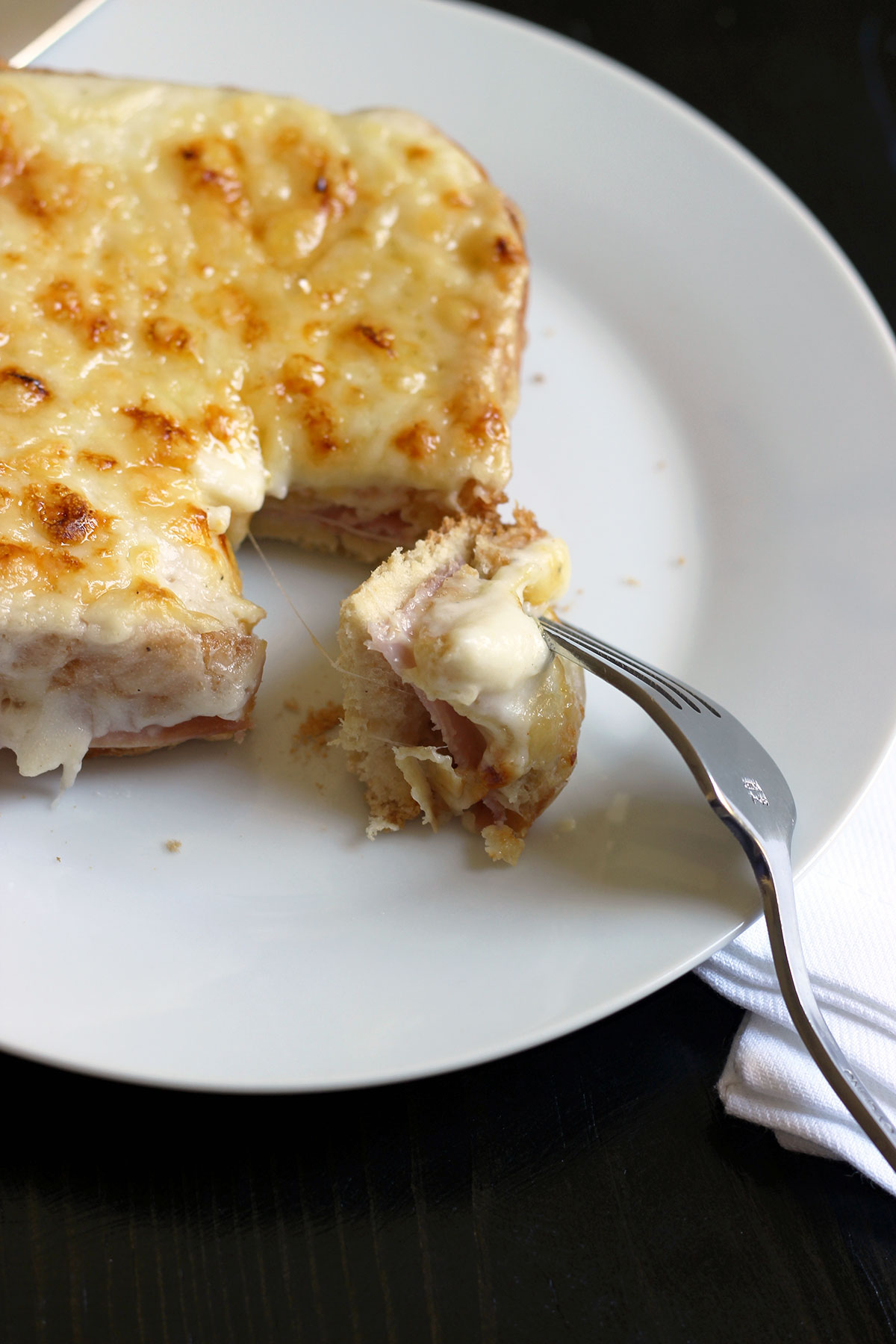 sandwich on plate with bite of croque monsieur with bechamel on fork.
