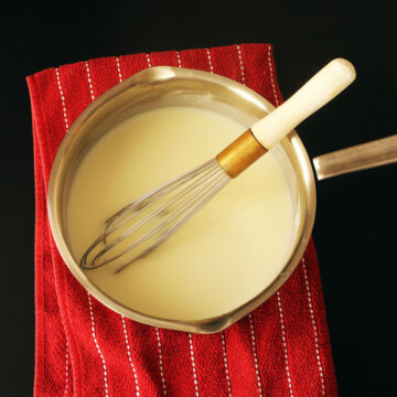 white sauce in pot with whisk