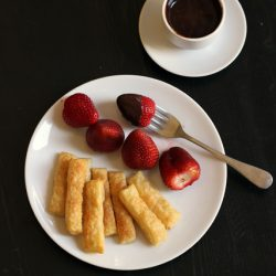 plate of cinnamon crisps and strawberries with an espresso cup of fondue