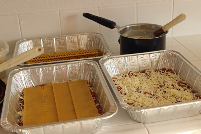 lasagna noodles layered in metal containers for freezing