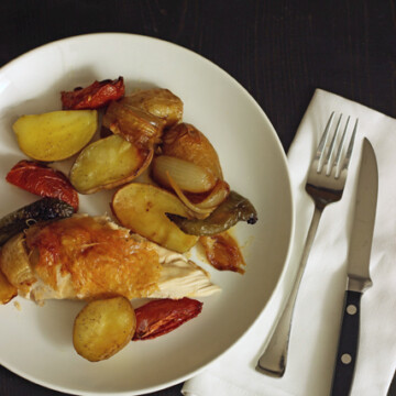 A plate of food with a fork and knife, with Roast chicken