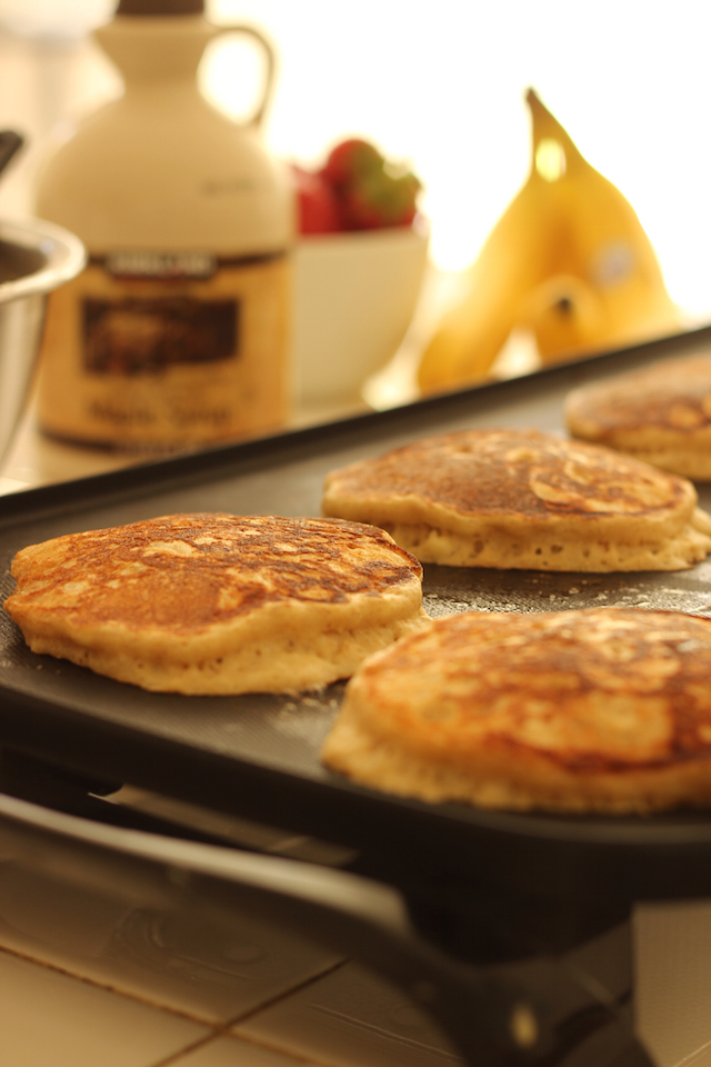 banana pancakes cooking on the griddle