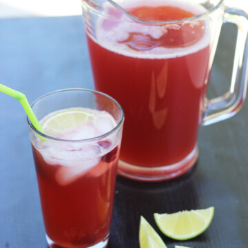 A glass of cherry Limeade and pitcher