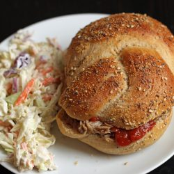 A plate with coleslaw and pulled pork sandwich