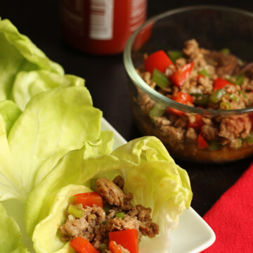 A close up of a lettuce wrap with turkey and peppers