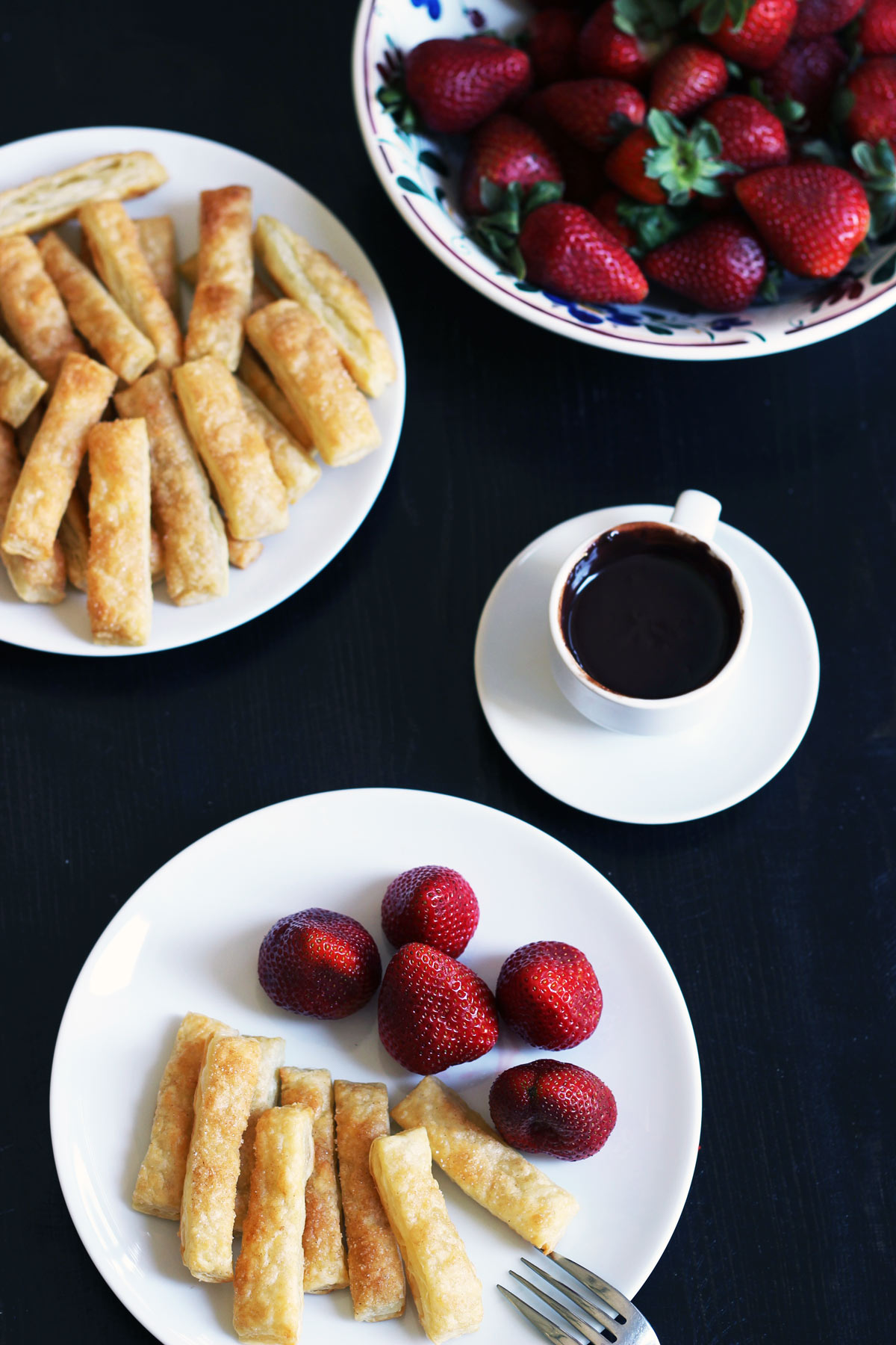 plates of puffs and berries with cup of chocolate fondue