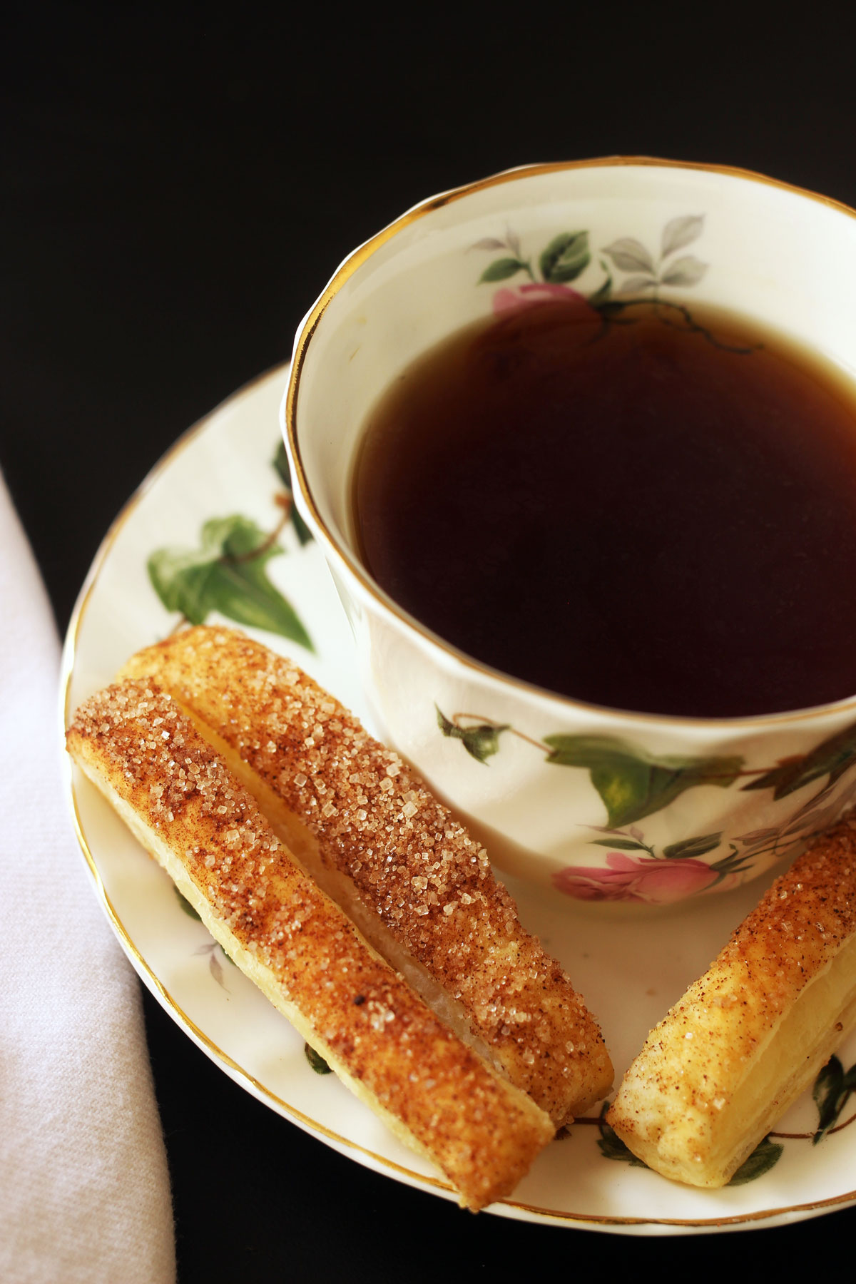 puffs on saucer with tea cup and napkin