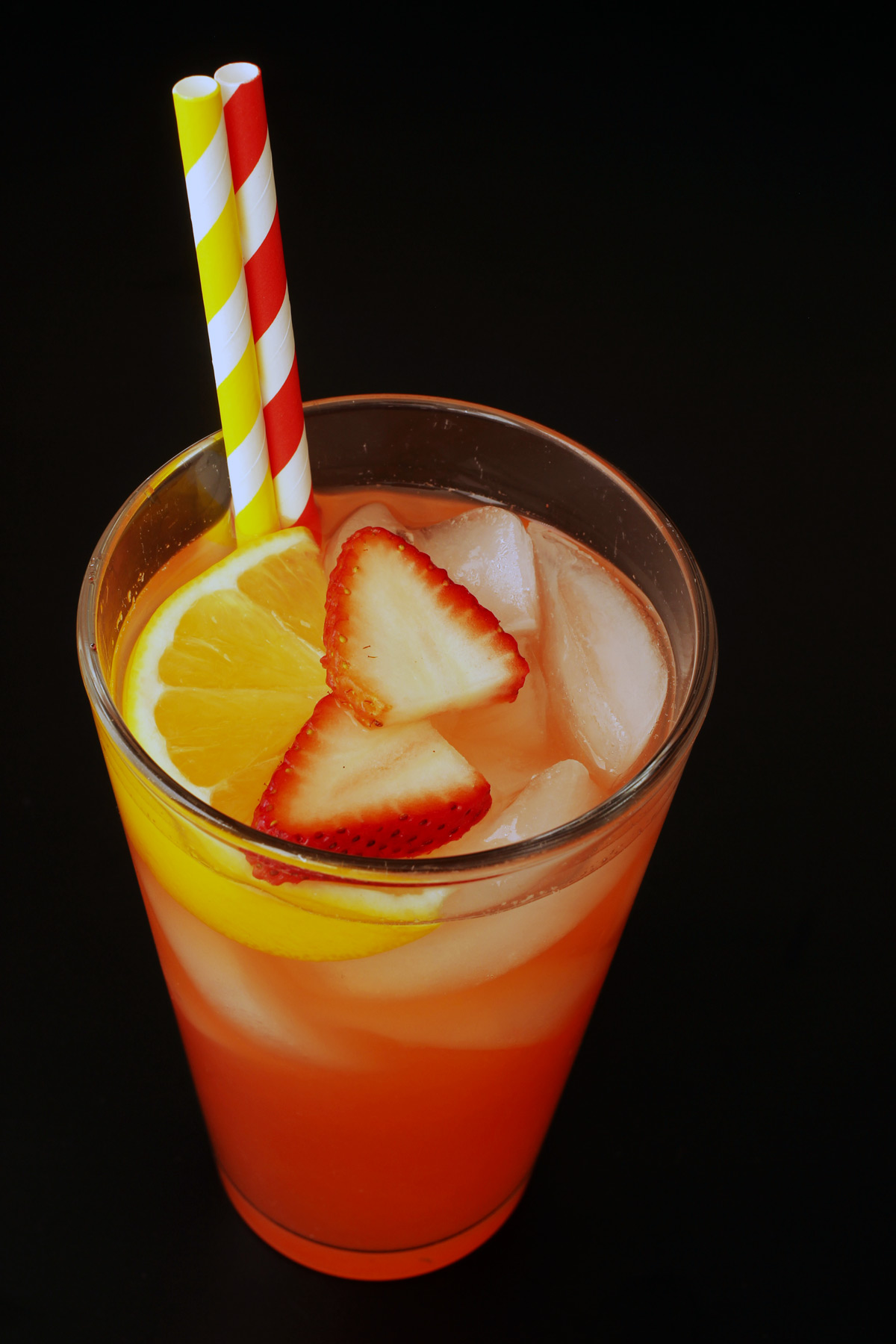 glass of lemonade with strawberry slices and lemon wedge on top of ice with straws