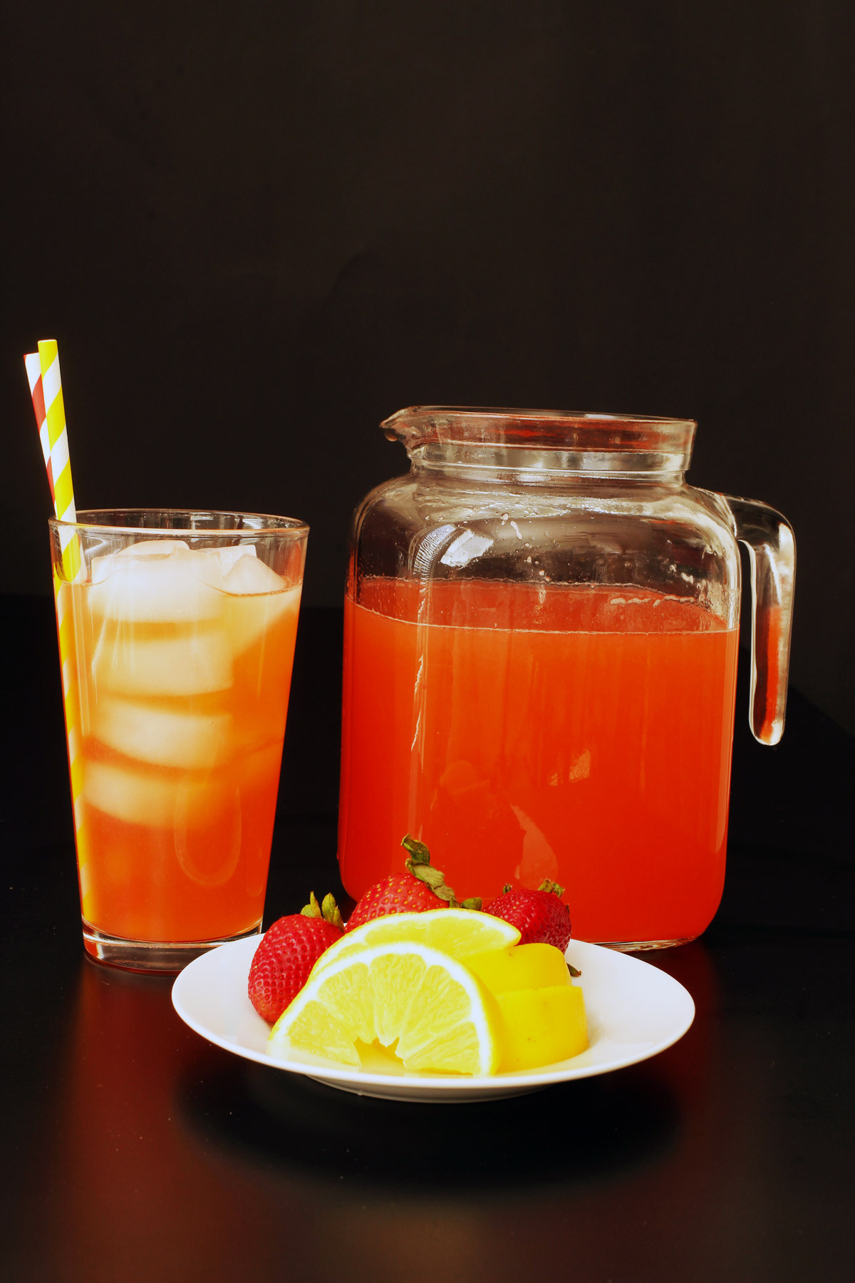 sideview of glass of lemonade, full pitcher, and plate of strawberries and lemon wedges