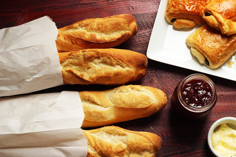 Baguette and croissants on table with jam