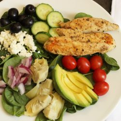 a greek salad with veggies and chicken