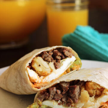 breakfast burrito cut in half, pitcher of orange juice