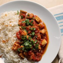 A plate of rice and chicken tikka masala