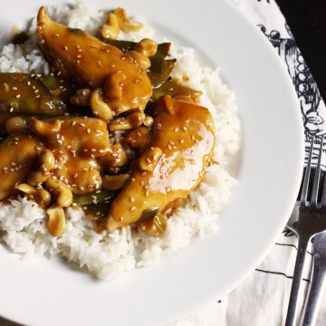 Cashew chicken atop rice on a plate