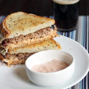 A reuben sandwich cut in half on a plate