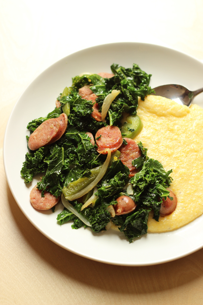 A plate of sausage and greens, with Polenta