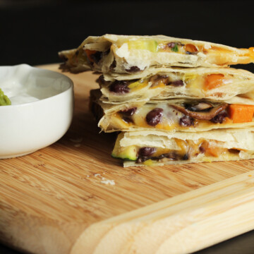 A quesadilla sitting on top of a wooden cutting board, with dish of sour cream