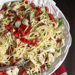 A bowl of spaghetti with chicken and tomatoes