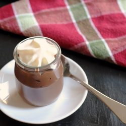 A cup of Chocolate Pudding on a plate with spoon