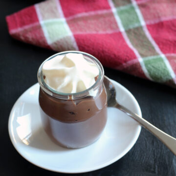 pot of chocolate pudding on plate with spoon