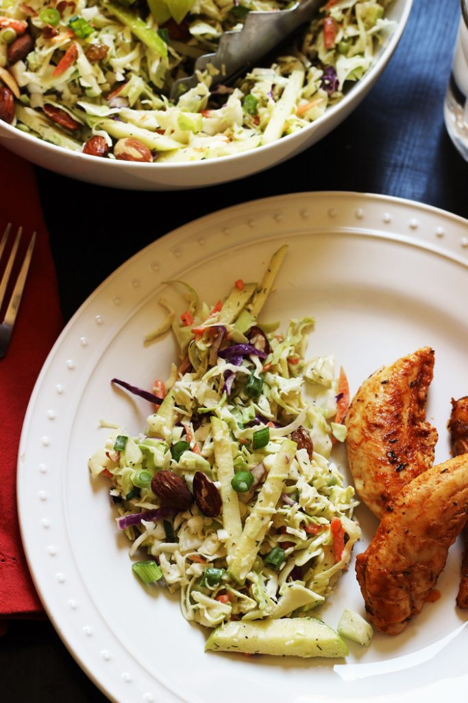 A plate of food on a table, with cole slaw and chicken