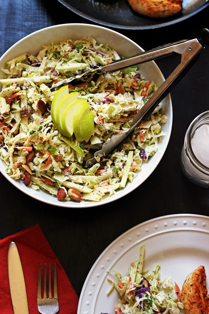 A bowl of cabbage slaw with apples and almonds